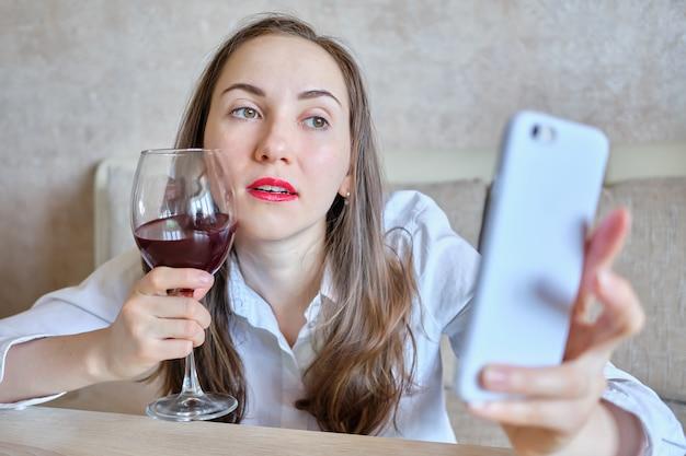 ワインを飲んで酔っ払った女の子が自撮り写真を撮ります。