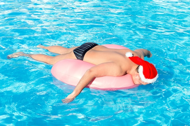 A drunk guy in santa claus hat swims on inflatable circle in the pool