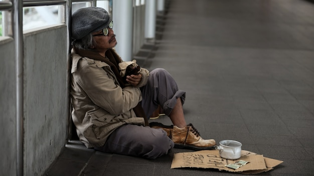 Drunk homeless old man or beggar drinking beer while asking for money donation at city sky walk.