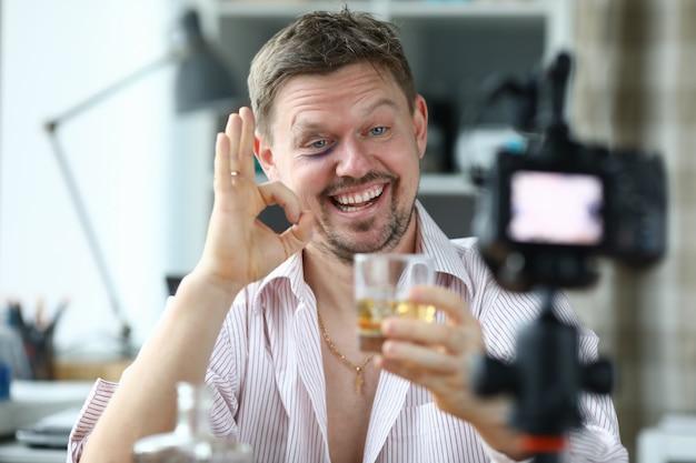酔って男性監督はウイスキーとグラスを保持