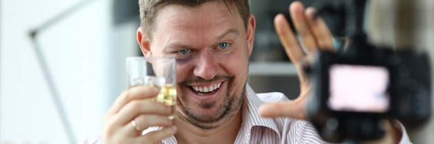 Drunk male director holds a glass with whiskey