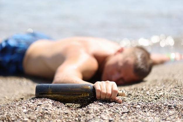 酔った男性の観光客は休暇の概念でアルコールを飲むワインのボトルとビーチに横たわっています
