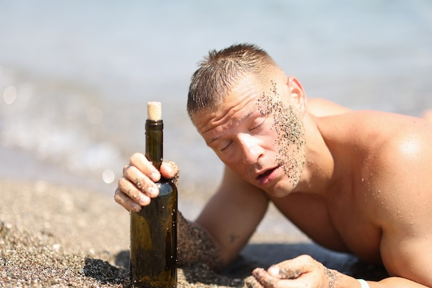 Drunk man on beach with closed eyes holding bottle of wine drinking alcohol in heat on beach