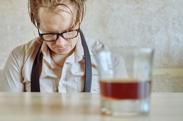 Пьяный мужчина в рубашке и галстуке пьет после увольнения с работы.
