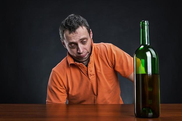 Пьяный мужчина смотрит на бутылку алкоголя
