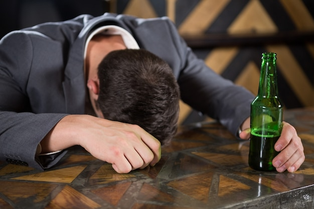 Drunk man lying on a counter with bottle of beer
