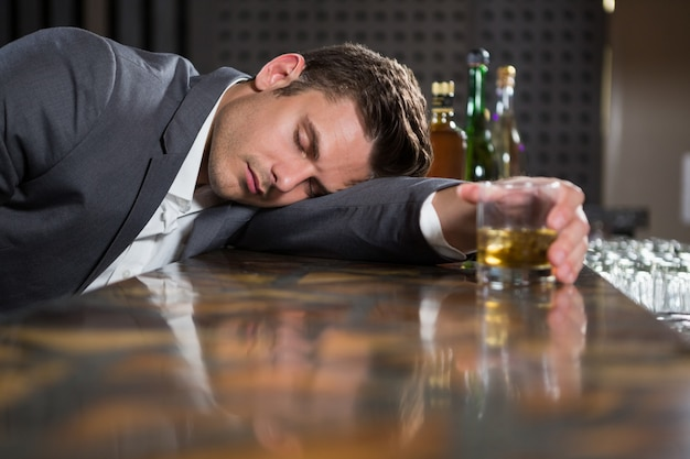 Drunk man lying on a counter with glass of whisky