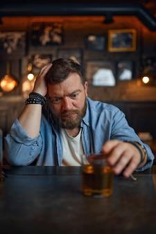 酔っぱらいはバーのカウンターでお酒を注ぐ。パブで休んでいる1人の男性、人間の感情や余暇活動、うつ病