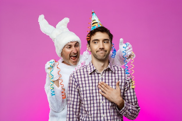 Drunk man and rabbit at birthday party over purple wall.