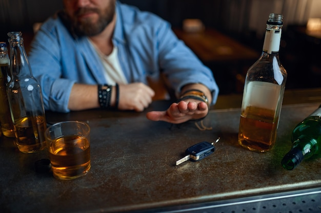 Drunk man refuses to drive under the influence of alcohol at the counter in bar