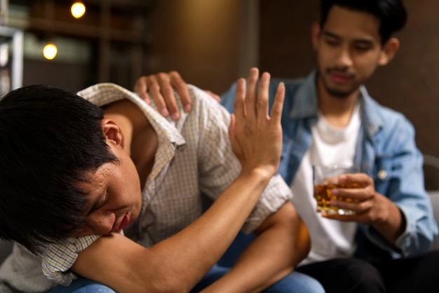 Drunk man sitting on sofa refusing whiskey from his friend by raising his hand to stop.