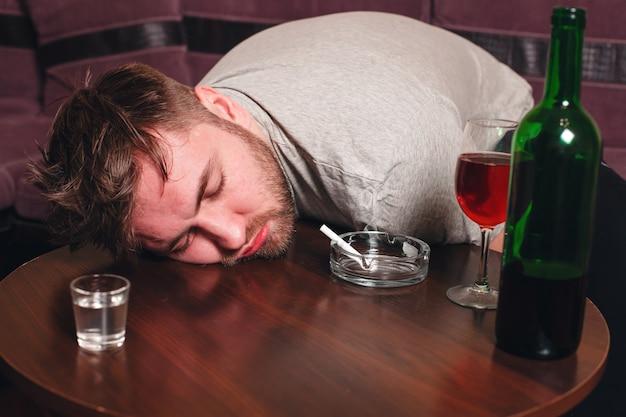 Пьяный человек спит на деревянном столе