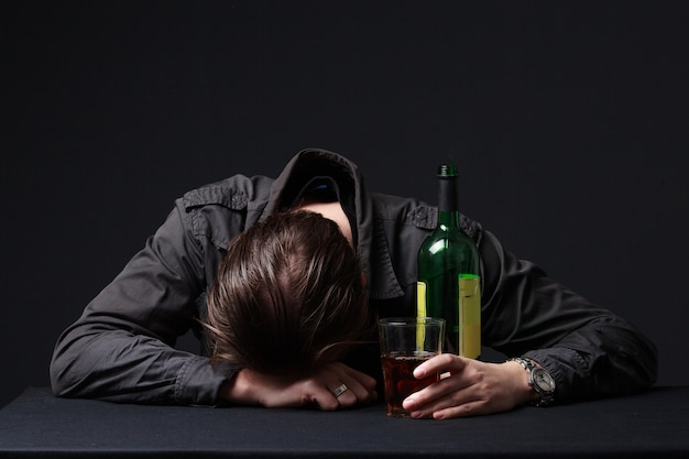 Drunk man sleeping on the table with a wineglass in the hand