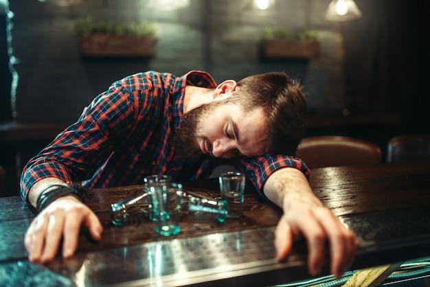 Пьяный мужчина спит за барной стойкой, алкогольная зависимость