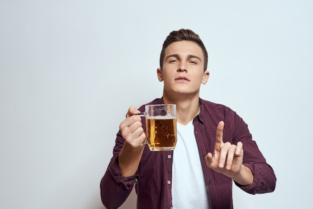 Пьяный мужчина с кружкой пива отпуск алкоголя образ жизни в красной рубашке эмоции свет