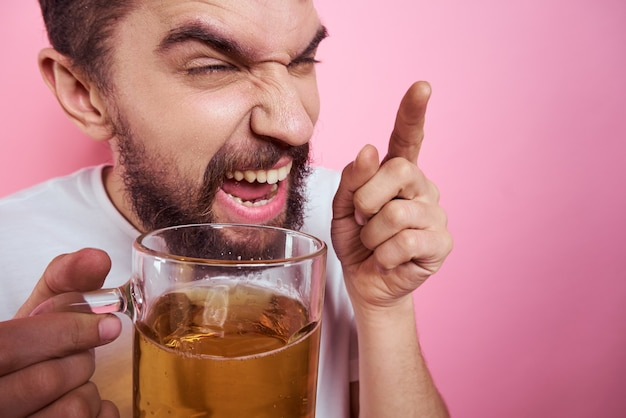 Drunk man with a large mug of beer on a pink background and a white t-shirt relaxed view of a thick beard mustache portrait. high quality photo