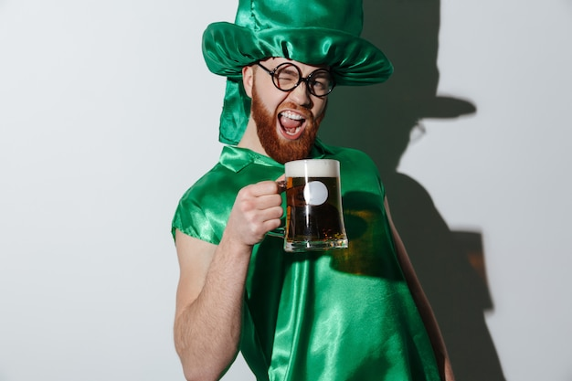 Drunk screaming man in st.patriks costume holding cup