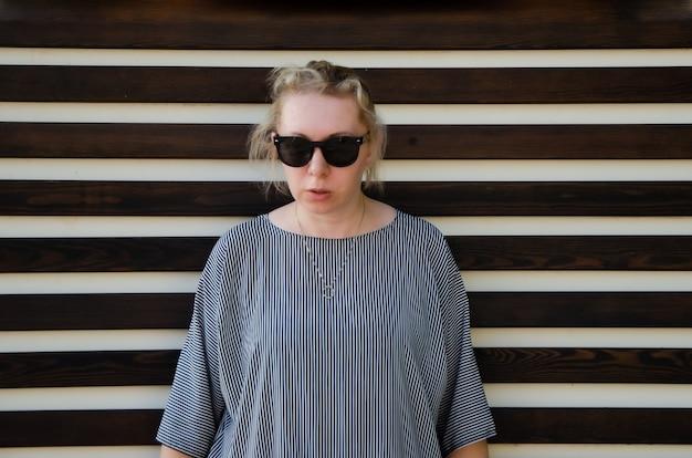 선글라스와 엄한 표정으로 긴장된 포즈의 취한 여자. 갈등을 준비하는 피곤한 분개하는 여자