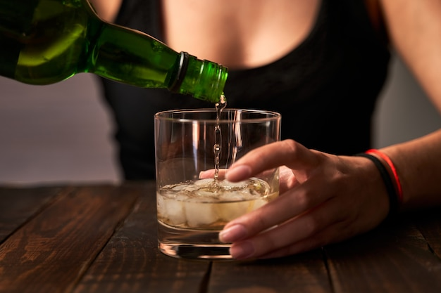 Drunk woman preparing a glass of alcohol. concept of alcoholism and addictions.