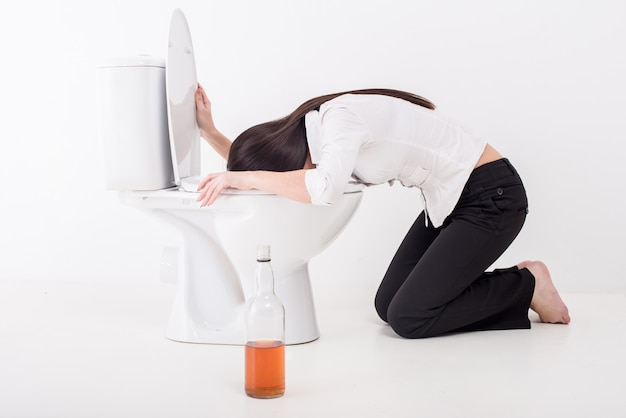 Drunk woman vomiting on a toilet bowl.