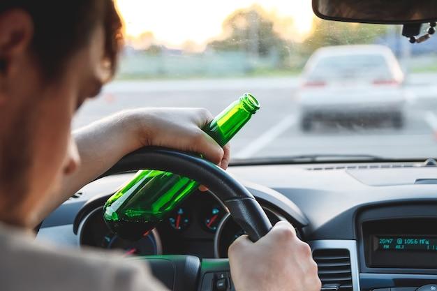 ビールのボトルで車を運転している酔った若い男。飲酒運転の概念をしないでください