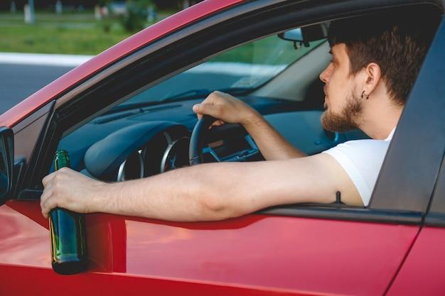 Пьяный молодой человек за рулем машины с бутылкой пива