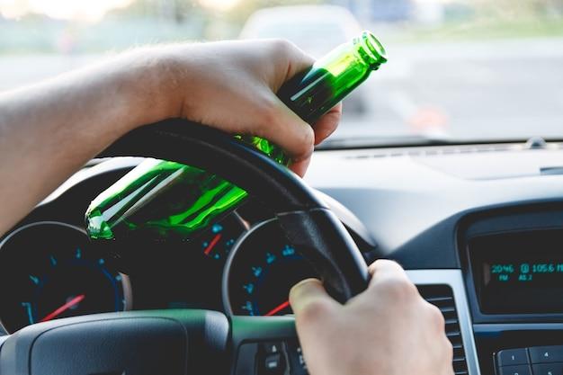 ビールのボトルが付いている車を運転して酔って若い男