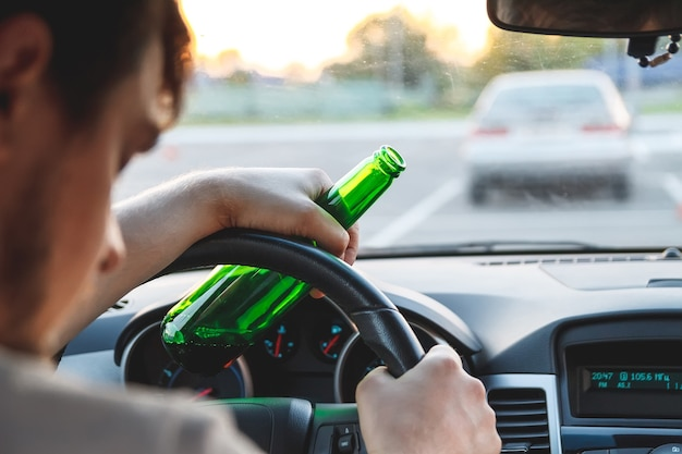 Drunk young man driving a car with a bottle of beer. don't drink and drive concept