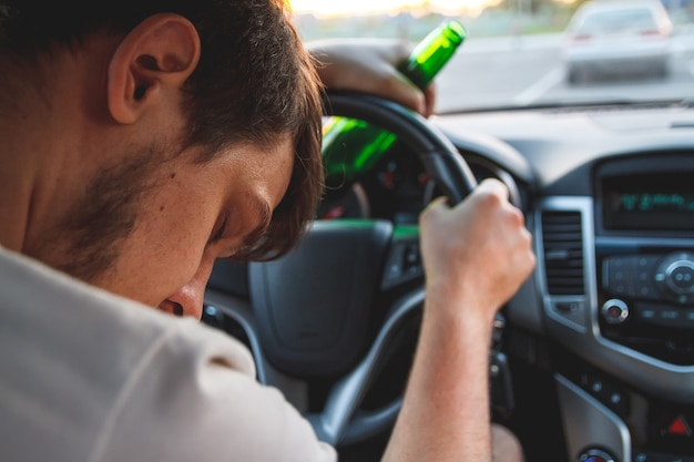 Drunk young man driving a car with a bottle of beer