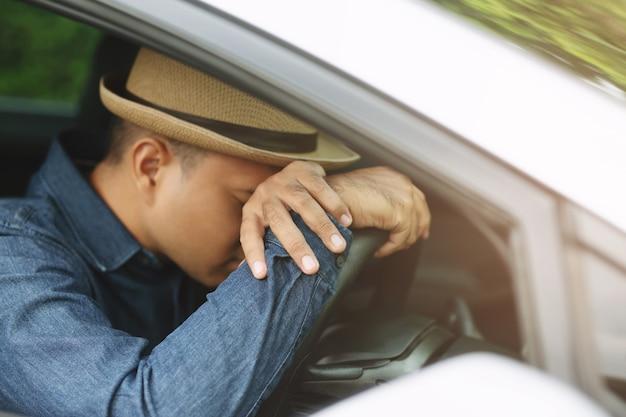 酔っ払った青年がハンドルにぶつかり、車の運転でぐっすり眠ります。旅行を運転している間眠いという概念、運転しないでください。