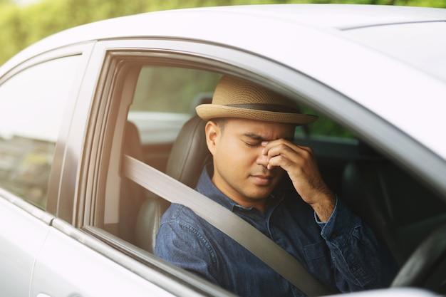 酔っ払った青年がハンドルにぶつかり、車の運転でぐっすり眠ります。旅行を運転しながら眠いコンセプト