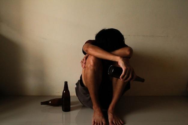 술에 취한 남자는 인생에서 스트레스를 받고 빈 방에 혼자 앉아 있고 슬프고 외롭고 학교, 청소년기, 가정 폭력, 원치 않는 사랑 문제, 혼자, 가족