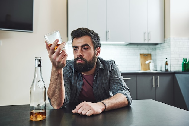 Drunkenness is nothing but voluntary madness drunk man with glass and bottle of whiskey sitting