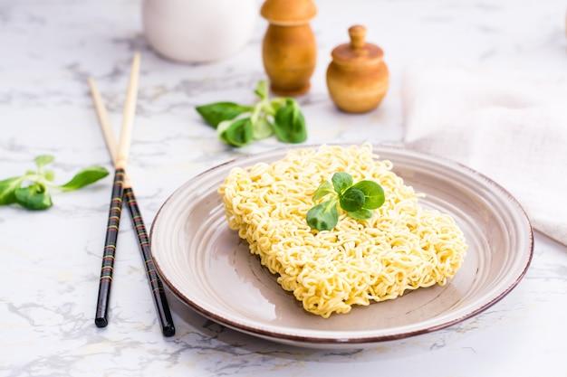 Сухая китайская лапша с листьями салата на керамической тарелке и палочками для еды