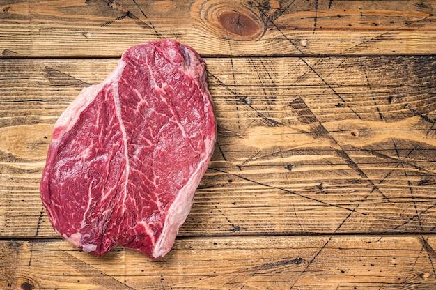 정육점 테이블에 말린 숙성된 원시 쇠고기 라운드 스테이크. 나무 배경입니다. 평면도. 공간을 복사합니다.
