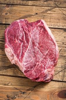 정육점 테이블에 말린 숙성된 원시 쇠고기 라운드 스테이크. 나무 배경입니다. 평면도.