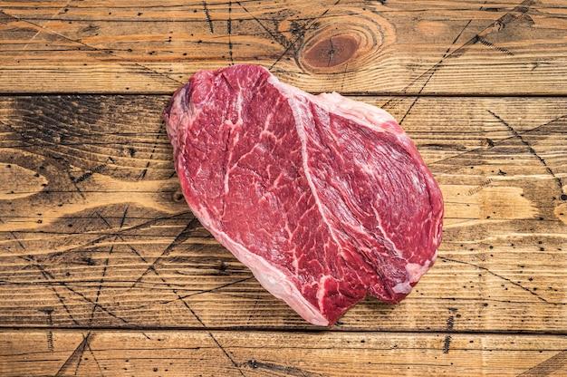 정육점 테이블에 말린 숙성된 생 쇠고기 둥근 스테이크. 나무 배경입니다. 평면도.