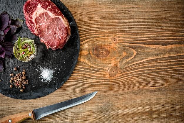 木製の背景にグリルするための材料を使用した乾燥熟成生ビーフステーキ。上面図。スペースをコピーします。静物。フラットレイ