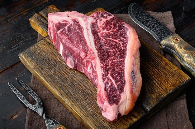 오래 된 어두운 나무 테이블에 나무 커팅 보드에 건조 숙성 원시 t-bone 또는 포터 하우스 쇠고기 차돌박이 고기 프라임 스테이크 세트