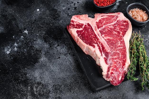 건조 숙성 된 원시 t-bone 또는 포터 하우스 쇠고기 고기 블랙 테이블에 허브와 소금을 곁들인 스테이크. 평면도.