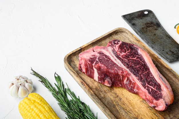 Сырое выдержанное на косточке или говядине стейк из говядины с травами и солью, на белом фоне, с местом для текста