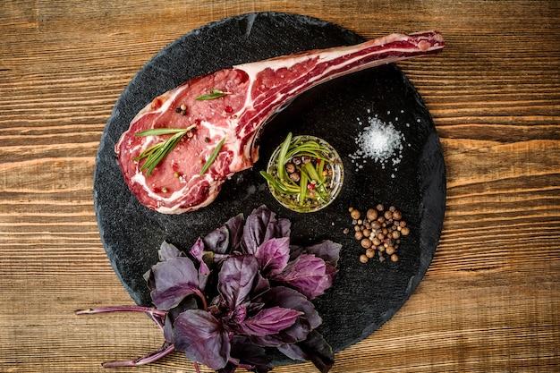 木製の背景にグリルするための材料を使用した乾燥熟成生トマホークビーフステーキ。上面図。スペースをコピーします。静物。フラットレイ