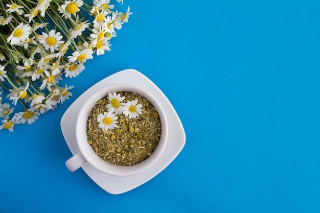 Сухие и свежие цветы ромашки в белой чашке