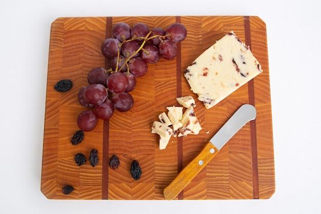Сухой и свежий виноград, сыр и нож