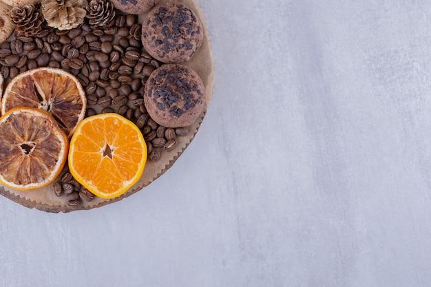 Сухие и сочные дольки апельсина, кофейные зерна, сосновые шишки и печенье на доске на белом фоне.