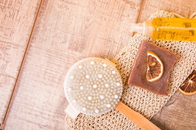 나무 표면에 마른 안티 셀룰 라이트 마사지 브러시, 니트 수건, 수제 코코아 비누, 말린 오렌지 슬라이스 및 바디 케어 오일