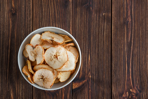 Dry apple in a bowl on a wooden background. top view. space for text