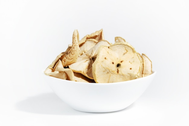 Dry apple chips in a white plate isolated on a white background. dehydrated food. a bunch of apple chips. healthy snack diet.
