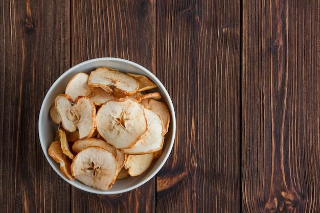 木製の背景上にボウルにリンゴを乾燥させます。上面図。テキストのためのスペース