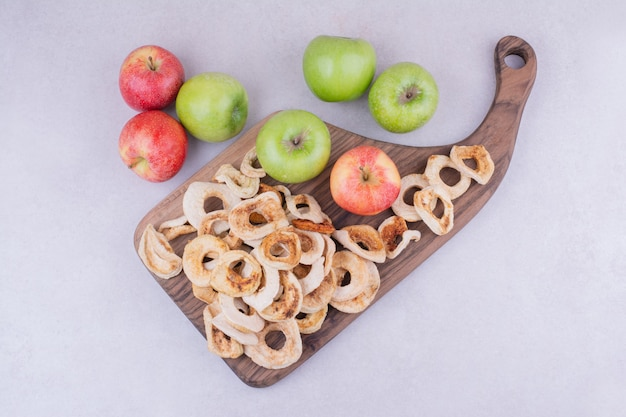 Dry apple slices on a wooden board with whole apples around